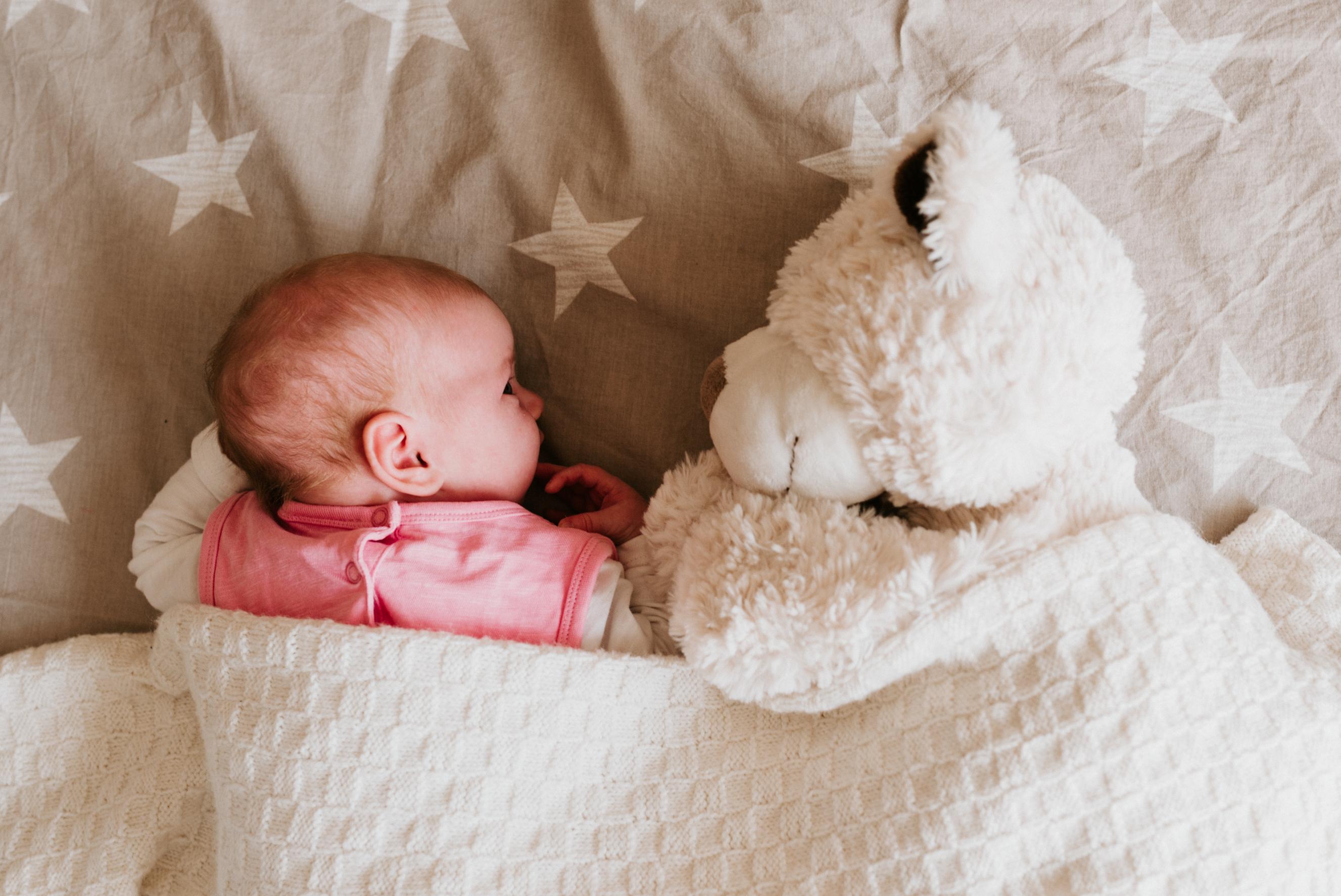 Baby mit Teddy beim Newborn Shooting auf einer Decke